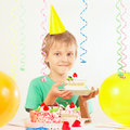 Little kid in holiday hat with piece of birthday cake and balloons Royalty Free Stock Photo