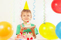 Little kid in holiday hat with piece of festive cake and balloons Royalty Free Stock Photo