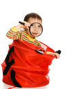 Little kid looking out of basket with a magnifying glass on a white background Royalty Free Stock Image