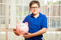 Little kid saving some money portrait of a cute nerdy boy carrying a piggy bank with his savings and smiling Stock Photo
