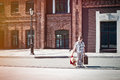 Little kid with suitcase and teddy bear toy crossing the sunny s is holding street in morning Royalty Free Stock Images