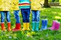 Little kids, boys or girls in jeans and yellow jacket in colorful rain boots