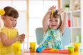Little kids having fun together with colorful modeling clay at daycare. Creative kids molding at home. Children girls