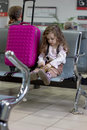 Little kit girl waiting for flight in airport hall Royalty Free Stock Photo