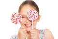 Little laughing girl holding colorful lollipop two big Royalty Free Stock Photography