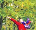Little laughing pretty girl in red coat throws yellow leaves in autumn park Royalty Free Stock Photo