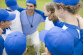 Little league baseball team in huddle with their coach