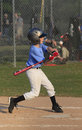 Little league batter begins his swing at a pitch young swings Stock Photo