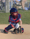Little league catcher goes for a pitch in the dirt going wild Royalty Free Stock Image