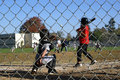 Little league players as seen through a wire fence from behind home base one player at bat another squatting in the catchers Stock Image
