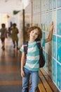 Little learner standing near lockers in school hallway Royalty Free Stock Photo