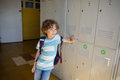 Little learner standing near lockers in school hallway Royalty Free Stock Photo
