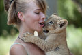 Little lion cub biting girl playing with a male Royalty Free Stock Image