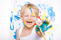 Little messy kid painting with paintbrush picture on easel. Education. Creativity. School. Preschool. Studio portrait over white b Royalty Free Stock Photo