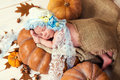 Little newborn baby girl in a lace bonnet  like Cinderella sleeping on a pumpkin Royalty Free Stock Photo