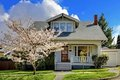 Little old cute house with a blooming cherry tree. Royalty Free Stock Photos