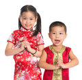Little oriental children wishing you a happy chinese new year girl and boy with traditional cheongsam standing isolated on white Royalty Free Stock Photos