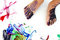 Little painted feet close up on a small child s that are covered in paint standing on a large blank white paper with colorful Stock Photography