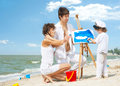 Little painter young parents looking at child painting picture on sea beach Stock Photography