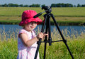 Little photographer with professional tripod river background outdoor Stock Images