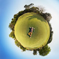 Little planet panorama of park. Man lies on the grass Royalty Free Stock Photo
