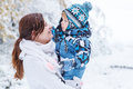 Little preschool boy and his mother playing with first snow in p park Stock Photo