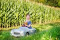 Little preschool kid girl driving big toy car and having fun with playing with big plush toy bear Royalty Free Stock Photo