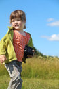 Little pretty girl holds camera and looks away at meadow in summer day Royalty Free Stock Images