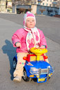 Little pretty girl sit on the toy car. Royalty Free Stock Photos