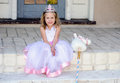 Little princess with toy unicorn a happy uses her imagination to pose her royal gown and tiara Royalty Free Stock Images