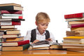 Little reader boy is reading interesting book high stacks of books are on the table near him Royalty Free Stock Photo