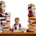 Little reader boy is reading interesting book high stacks of books are on the table near him Royalty Free Stock Images