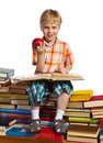 Little reader boy is reading interesting book he is setting on high stacks of books he holds apple in his hand Stock Photography
