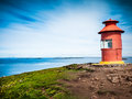 Little red lighthouse situated at the top of a cape over a sunny seascape related concept navigation help aid guide stykkisholmur Stock Photo