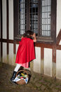 Little red riding hood looking through window Royalty Free Stock Image
