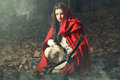 Little red riding hood waiting the prey beautiful wolf with crossbow in a foggy forest Stock Images