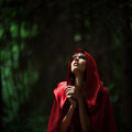 Little red riding hood in the wild forest beautiful dark haired girl a cloak was lost story fairy tale and legend grain Royalty Free Stock Photography