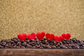 Little red satin hearts with letters on coffee beans with gold background, valentines day or wedding day celebrating