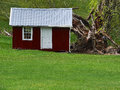 Little red shed a with metal roof stands out as landscape feature at edge of lawn Stock Photography