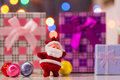 Little red toy santa claus with festive gifts christmas balls and arland lights on background new year decoration Royalty Free Stock Photos