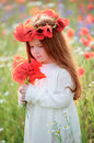 Little redhead girl with white dress on the green wheat field wi Royalty Free Stock Photo