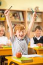 Little redhead schoolboy behind school desk during lesson Royalty Free Stock Image