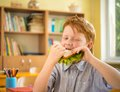 Little redhead schoolboy eating sandwich in class Royalty Free Stock Photography