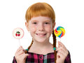 Little redheaded girl with freckles holding colored candies in hands Royalty Free Stock Photo