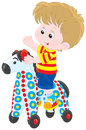 Little rider boy riding on a colorful toy horse Royalty Free Stock Photography