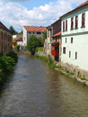 Little river bordered by old buildings and greenery peaceful Stock Image