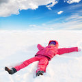 Little ruddy nice girl in winter outwear lies in snow and smiles Stock Photos