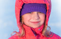 Little ruddy nice girl in winter outwear smiles Royalty Free Stock Photography