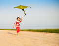 Little running girl with flying kite on beach at sunset Royalty Free Stock Photo