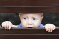 Little sad boy looking out through fence portrait of abandoned by parents baby with staring blue eyes and lonely face expression Royalty Free Stock Photo
